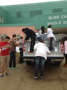 Students measure to calculate # of soup cans needed to fill the back of the  truck