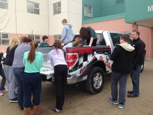 Students measure Steve Webster's, Sales & Finance Consultant, Ford F-150 to begin calculating